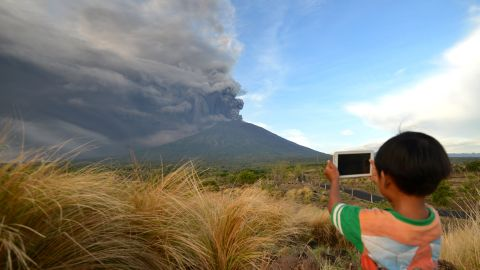 A boy takes pictures during Mount Agung's eruption on Indonesia's resort island of Bali on November 26,