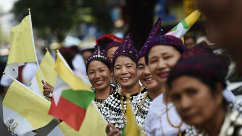 Ethnic Kachin people in traditional dress wait along a street in Yangon on Monday with the hopes of seeing Pope Francis on his way from the airport after arrival.