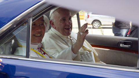 Pope Francis, right, waves upon arrival at Yangon International Airport on Monday in Yangon, Myanmar.
