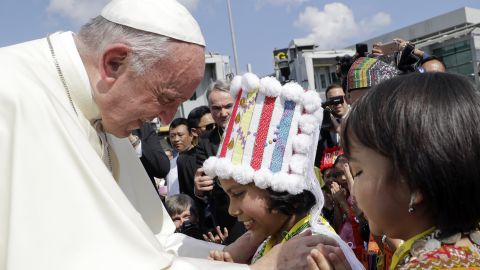 Pope Francis is greeted by young children in traditional clothes upon his arrival at Yangon's airport in Myanmar.