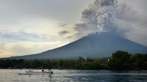 A fisherman drives a traditional boat as Mount Agung erupts in Bali on November 28.