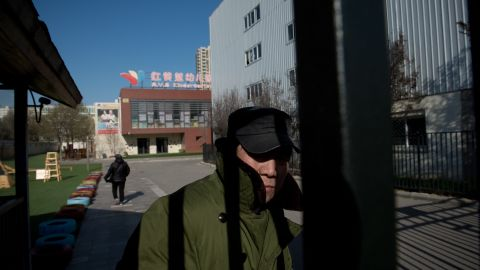 A security guard stands behind the gate of the RYB Education New World kindergarten in Beijing.