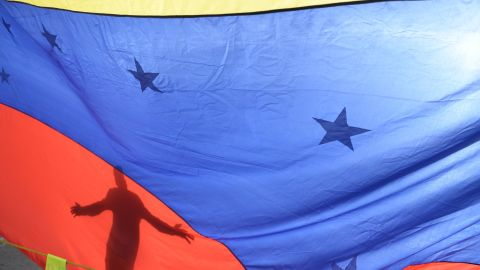 A person's shadow is cast on a Venezuelan national flag in Caracas on July 10, 2017. Venezuela hit its 100th day of anti-government protests Sunday, amid uncertainty over whether the release from prison a day earlier of prominent political prisoner Leopoldo Lopez might open the way to negotiations to defuse the profound crisis gripping the country. / AFP PHOTO / FEDERICO PARRA        (Photo credit should read FEDERICO PARRA/AFP/Getty Images)