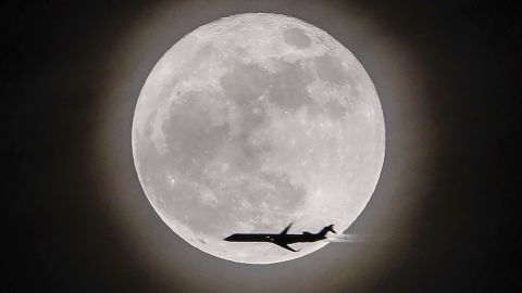 An airplane crosses in front of the moon, seen in Avondale Estates, Georgia.