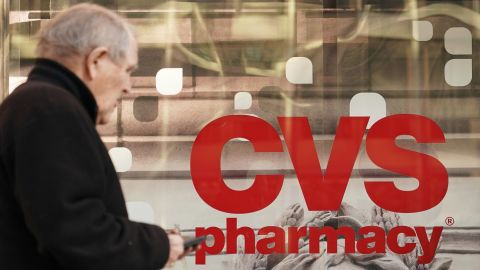 Pedestrians walk past a CVS pharmacy in Washington, DC on December 3, 2017.  US pharmacy chain CVS has agreed to buy medical insurer Aetna for around $69 billion, according to reports. / AFP PHOTO / MANDEL NGAN        (Photo credit should read MANDEL NGAN/AFP/Getty Images)