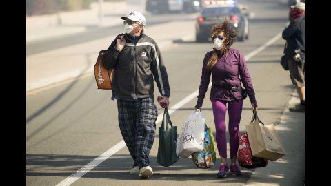 James and Josie Ralstin carry belongings retrieved from their home in Ventura on December 5.
