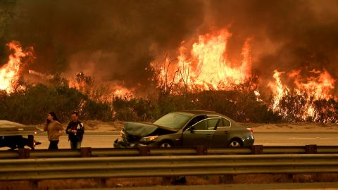 A woman involved in a traffic accident waits to get towed beside a wall of flames on the 101 highway during the Thomas wildfire near Ventura, California on December 6, 2017.  California motorists commuted past a blazing inferno Wednesday as wind-whipped wildfires raged across the Los Angeles region, with flames  triggering the closure of a major freeway and mandatory evacuations in an area dotted with mansions. / AFP PHOTO / Mark RALSTON        (Photo credit should read MARK RALSTON/AFP/Getty Images)