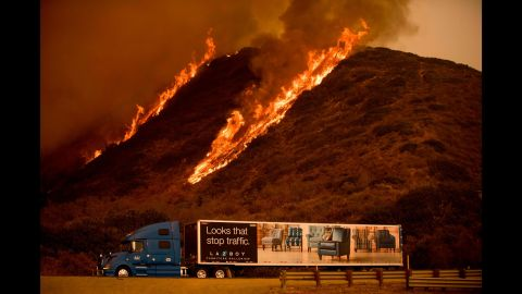 Flames from the Thomas Fire burn above a truck north of Ventura on December 6.