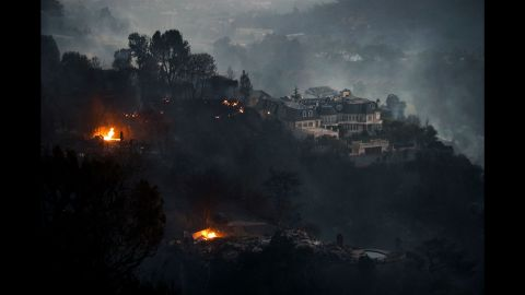 Fires surround a hilltop mansion in Los Angeles on Wednesday, December 6.