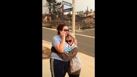Joyce George, right, comforts neighbor Dawn Reily on December 6. Reily's Ventura home was destroyed by fire.