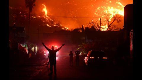 Residents watch the Thomas Fire burn a hillside above La Conchita, California, on December 7.