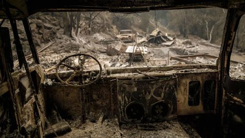 The shell of a burnt-out bus is seen after fire swept through residential neighborhoods near Ojai on Friday, December 8.