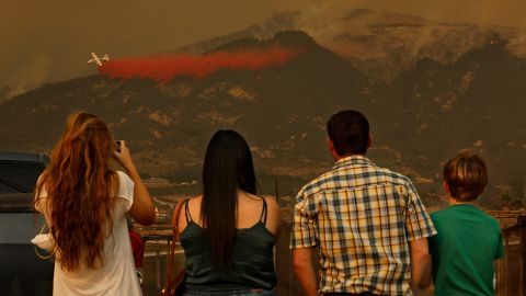 People watch as firefighters battle flames in Carpinteria, California, on Monday, December 11.