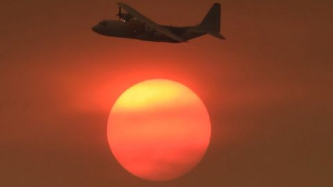 As smoke obscures the sun, a Coulson C-130 air tanker turns to make a drop on a Carpinteria hillside on December 11.