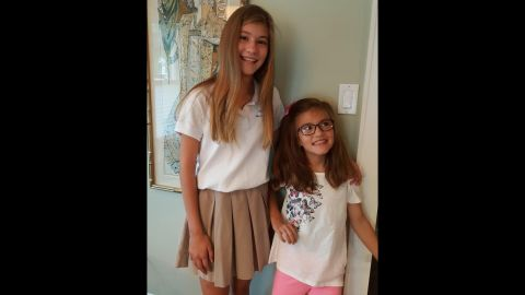 """Avery and her sister Presley took a first-day-of-school photo in August 2016. Presley helped Avery stand up by leaning her against the wall.  """"Avery loves school and was so excited to be heading back to school after her August break,"""" her father said."""