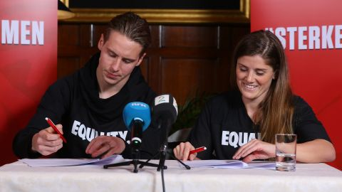 Stefan Johansen (L) and Maren Mjelde (R) sign the agreement in London.