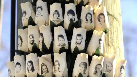 """Roses with the faces of the Sandy Hook Elementry students and adults  killed are seen on a pole in Newtown, Connecticut on January 3, 2013.  Students at the elementary school where a gunman massacred 26 children and teachers last month were returning Thursday to classes at an alternative campus described by police as """"the safest school in America."""" Survivors were finally to start their new academic year in the nearby town of Monroe, where a disused middle school has been converted and renamed from its original Chalk Hill to Sandy Hook. AFP PHOTO / TIMOTHY A. CLARY / AFP / TIMOTHY A. CLARY        (Photo credit should read TIMOTHY A. CLARY/AFP/Getty Images)"""