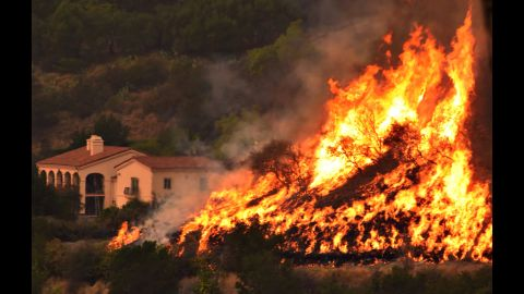 """Flames from a back-firing operation rise behind a home off Ladera Lane near Bella Vista Drive in Santa Barbara, California, on Thursday, December 14. Powerful Santa Ana winds and extremely dry conditions are fueling <a href=""""http://www.cnn.com/2017/12/07/us/ventura-fire-california/index.html"""" target=""""_blank"""">wildfires in Southern California</a> in what has been a devastating year for <a href=""""http://www.cnn.com/interactive/2017/12/us/california-wildfires-cnnphotos/"""" target=""""_blank"""">such natural disasters in the state.</a>"""