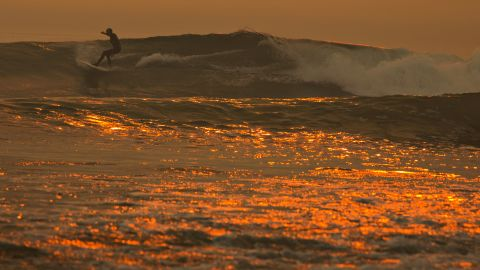 A smoke-filled sky filters sunlight to orange around a surfer as the Thomas Fire continues to grow and threaten communities from Carpinteria to Santa Barbara on Tuesday, December 12, in Carpinteria, California.