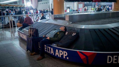 A traveler sleeps on a baggage carousel at Hartfield-Jackson Atlanta International Airport on Sunday.