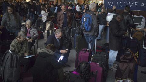 Passengers wait in a dark terminal at Hartsfield-Jackson International Airport.