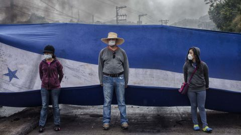 Protesters hold a Honduran flag as they block a road during protests against the presidential election of Juan Orlando Hernandez in Tegucigalpa, Honduras, on Monday, Dec. 18, 2017.