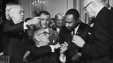 US President Lyndon B. Johnson shakes the hand of Dr. Martin Luther King Jr. (1929  - 1968) at the signing of the Civil Rights Act while officials look on, Washington DC. (Photo by Hulton Archive/Getty Images)