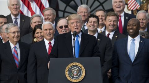 """US President Donald Trump flanked by Republican lawmakers speaks about the passage of tax reform legislation on the South Lawn of the White House in Washington, DC, December 20, 2017. Trump hailed a """"historic"""" victory Wednesday as the US Congress passed a massive Republican tax cut plan, handing the president his first major legislative achievement since taking office nearly a year ago. / AFP PHOTO / SAUL LOEB        (Photo credit should read SAUL LOEB/AFP/Getty Images)"""