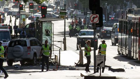 A white SUV (L) sits in the middle of the road as police and emergency personnel work at the scene of where a car ran over pedestrians in Flinders Street in Melbourne on December 21, 2017.The car ploughed into a crowd in Australia's second-largest city on December 21, injuring at least a dozen people, some of them seriously, officials said. / AFP PHOTO / Mark Peterson        (Photo credit should read MARK PETERSON/AFP/Getty Images)