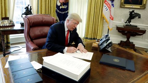 """President Donald Trump signs into law a $1.5 trillion tax overhaul package, Friday, Dec. 22, 2017, in the Oval Office of the White House in Washington. Trump touted the size of the tax cut, declaring to reporters in the Oval Office before he signed it Friday that """"the numbers will speak."""" (AP Photo/Evan Vucci)"""