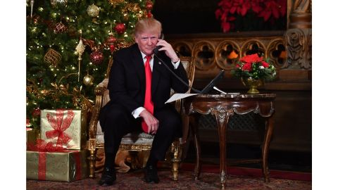 """US President Donald J. Trump participates in NORAD Santa Tracker phone calls at the Mar-a-Lago resort in Palm Beach, Florida on December 24, 2017.  """"NORAD Tracks Santa"""" is an annual Christmas-themed entertainment program, which has existed since 1955, produced under the auspices of the North American Aerospace Defense Command. / AFP PHOTO / Nicholas Kamm        (Photo credit should read NICHOLAS KAMM/AFP/Getty Images)"""
