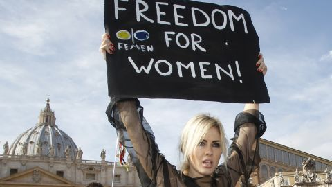 """An activist of the Ukrainian female rights organization """"Femen"""" shows a placard during a protest in St. Peter's Square at the Vatican, Sunday, Nov. 6, 2011. (AP Photo/Pier Paolo Cito)"""