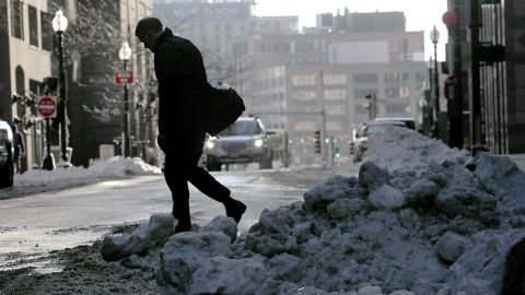 With snow on the ground, a person walks across the street on Tuesday, Dec. 26, 2017, in Boston. The storm that gave New England a white Christmas has moved out and is being replaced by dangerous cold. Temperatures in Massachusetts, Connecticut and Rhode Island are not expected to rise out of the 20s all week and could dip into the single digits. (Suzanne Kreiter/The Boston Globe via AP)