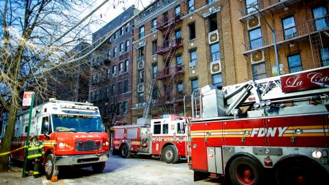 Fire personnel work on the scene of a Bronx apartment fire on December 29.