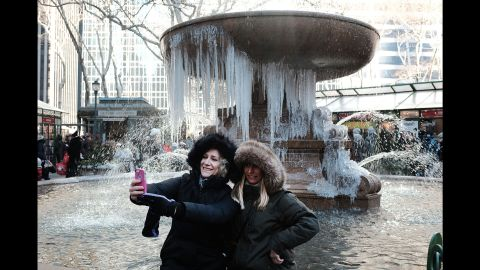 Two women take a selfie in front of a partially frozen fountain in New York City on Wednesday, December 27.