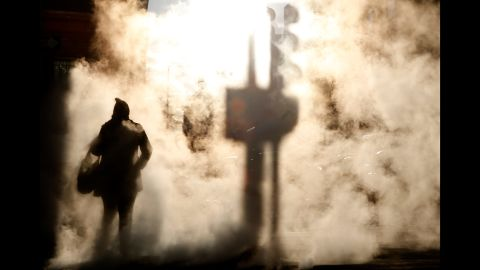 A person walks by a steam vent in Boston on December 27.
