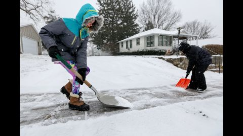 Karlee Winter and her brother Samuel Espinoza shovel snow from their neighbor's sidewalk in Dubuque, Iowa, on December 28.