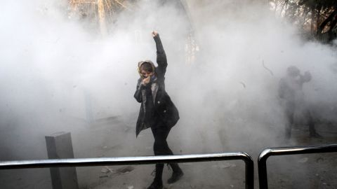An Iranian woman raises her fist amid the smoke of tear gas at the University of Tehran during a protest driven by anger over economic problems, in the capital Tehran on December 30, 2017. Students protested in a third day of demonstrations sparked by anger over Iran's economic problems, videos on social media showed, but were outnumbered by counter-demonstrators. / AFP PHOTO / STR        (Photo credit should read STR/AFP/Getty Images)