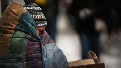 A homeless man tries to stay warm on a Manhattan street on an unseasonably cold day on March 15, 2017 in New York City. (Photo by Spencer Platt/Getty Images)