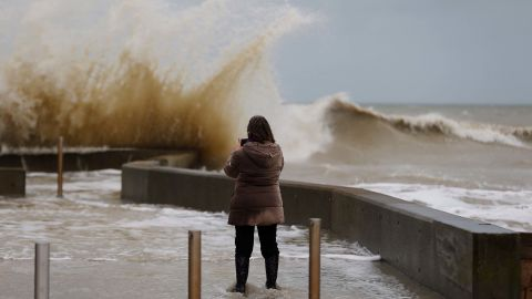 A woman takes photos of waves crashing against a tidal wall Thursday in Asnelles, northwestern France.