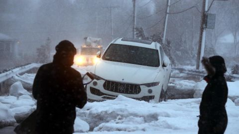 A man checks out an abandoned vehicle trapped in sea ice during the storm Thursday in Scituate.