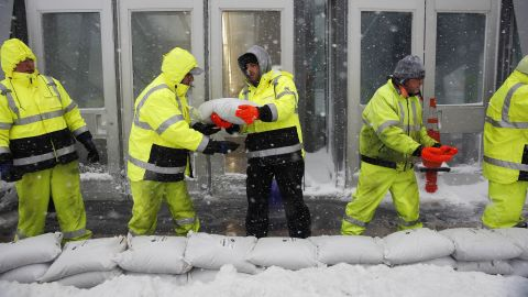 Workers on January 4 place sandbags in front of the Aquarium subway station to protect against flooding from Boston Harbor in Boston.