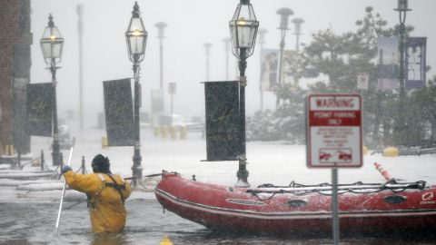 A firefighter wades through floodwaters from Boston Harbor on Long Wharf on Thursday.