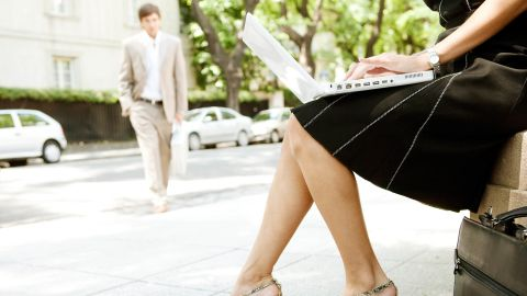 Part section of a young businesswoman working on her laptop computer while sitting in a classic street in the city with another businessman walking by.; Shutterstock ID 116534125; Job: -