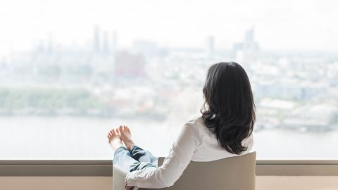 Quality of life concept of business woman rear view relaxing sitting in rest on armchair in modern hotel guest room or luxury home living room looking outward to city urban scene; Shutterstock ID 672164257; Job: -