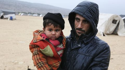 A Syrian man who fled from the outskirts of southern Idlib due to conflict between government forces and opposition fighters stands holding a child following their arrival at the make-shift camp of Kalbeed near the Bab al-Hawa crossing on the Syria-Turkey border on January 4, 2018.   Government and allied forces backed by Russian warplanes have been battling jihadist fighters and rebels for over a week in an area straddling the border between Idlib and Hama provinces. / AFP PHOTO / Zein Al RIFAI        (Photo credit should read ZEIN AL RIFAI/AFP/Getty Images)