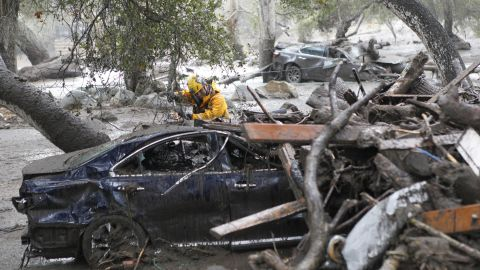 A member of the Long Beach search and rescue team looks for survivors in a car in Montecito on January 9, 2018.