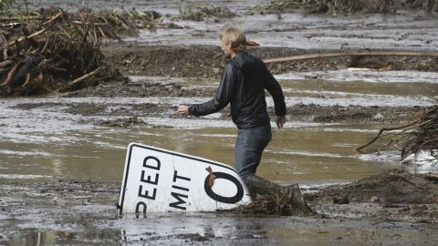 Phillip Harnsberger crosses through mud from a flooded creek in Montecito on January  9, 2018.