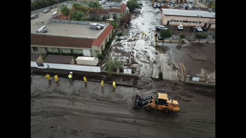 Los Angeles firefighters work amid floodwaters and mud on January 9, 2018.
