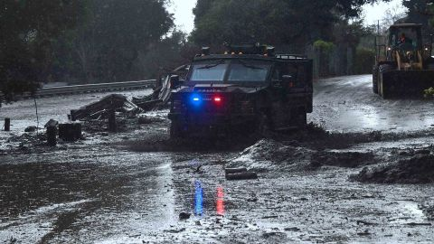 A police vehicle drives across a flooded side road in Montecito, near the San Ysidro exit of Highway 101 on January 9, 2018.